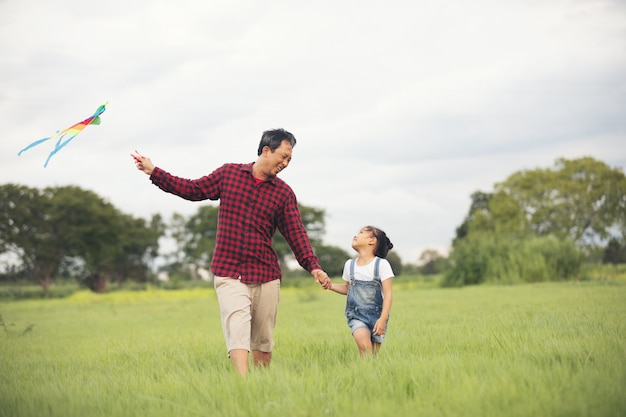 Muchacha y padre asiáticos del niño con una cometa que corre y feliz en prado en verano en naturaleza