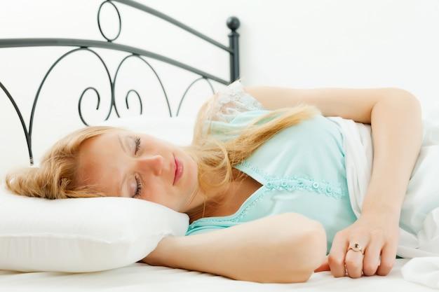 Muchacha de pelo largo que duerme en su cama