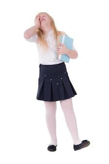 Muchacha con el pelo rubio en el uniforme escolar que presenta en el aislante blanco
