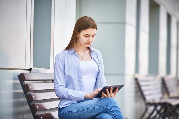 Muchacha pensativa joven que se sienta en un banco con una tableta en mano.