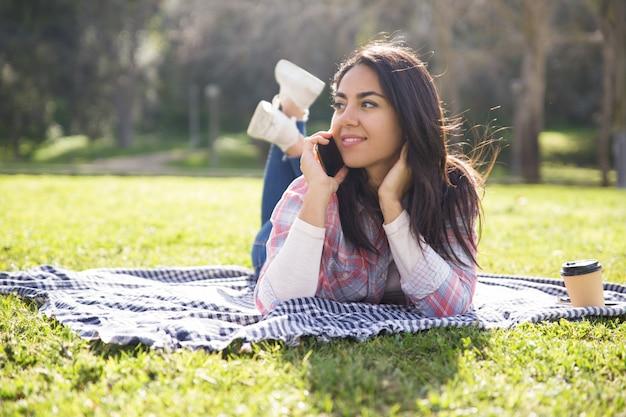 Muchacha pensativa sonriente que descansa sobre hierba y que habla en la célula