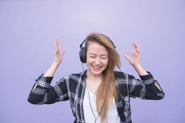 La muchacha positiva en ropa casual escucha la música en los auriculares, aislados en un fondo púrpura. retrato de una mujer feliz escuchando música sobre un fondo morado