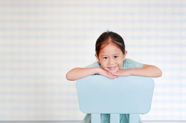 La muchacha preescolar del niño asiático feliz en un cuarto de jardín de infancia presenta en silla plástica del bebé.