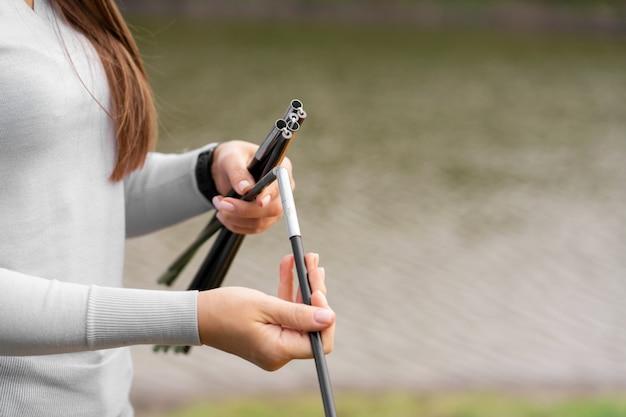 Muchacha del primer que sostiene las barras para la tienda de campaña. camping con carpa. lago en el
