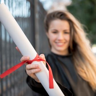 Muchacha del primer en su graduación que sostiene el certificado