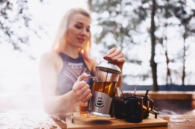 Muchacha que bebe té caliente mientras que se sienta en el invierno fuera del balneario caliente