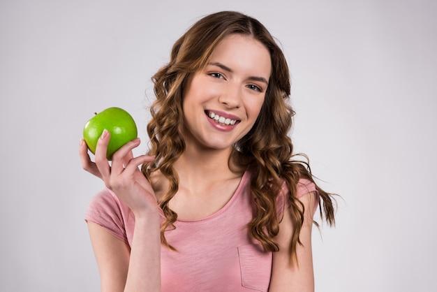Muchacha que celebra la sonrisa verde de la manzana aislada.