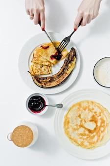 Muchacha que come las crepes con el atasco del arándano, desayuno con café.