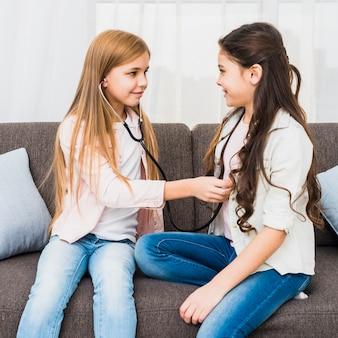 Muchacha que controla el latido del corazón de su amigo con el estetoscopio que se sienta en el sofá