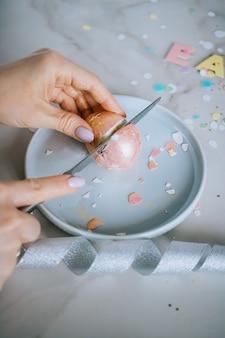 Muchacha que corta los huevos de pascua de oro en el fondo de mármol, confeti, chispas, cintas.