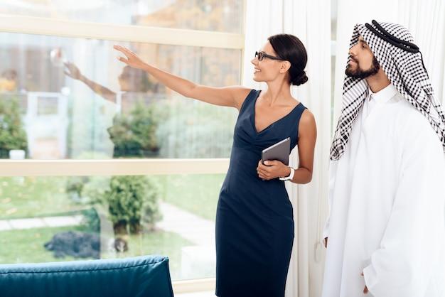 Muchacha que habla con los hombres de negocios árabes en un negocio.