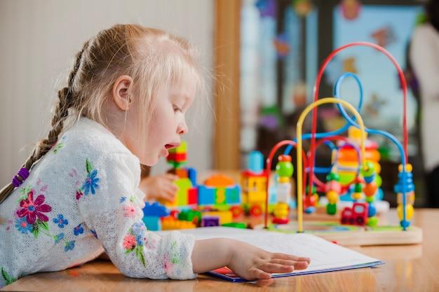 Muchacha que lee en jardín de la infancia