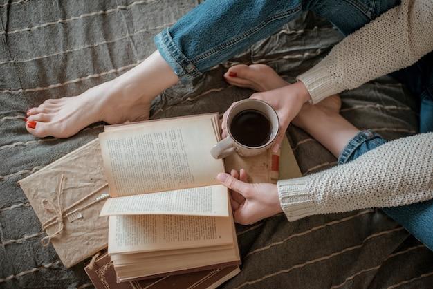 Muchacha que lee un libro y que bebe el café en pies de la cama en la pared.