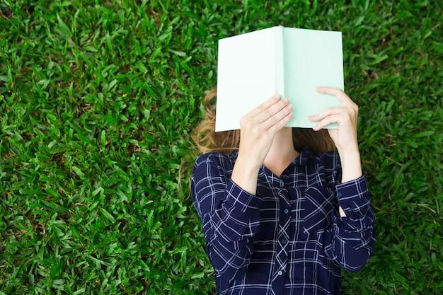 Muchacha que miente en la hierba y el libro de lectura Foto gratis