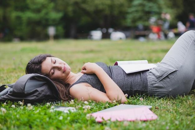 Muchacha que miente en hierba en parque