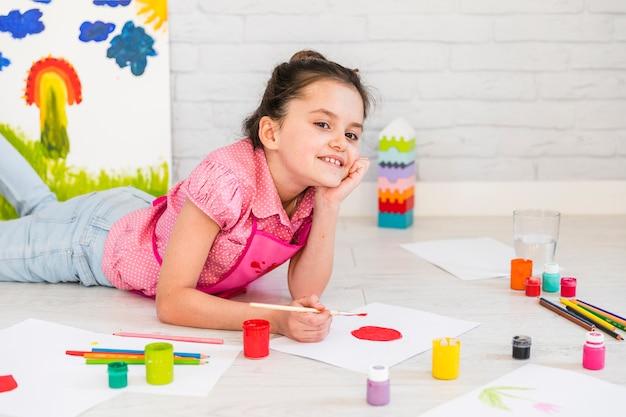Muchacha que miente en la pintura del piso en el libro blanco con el cepillo de pintura