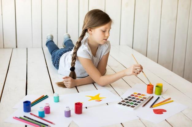 Muchacha que miente en la pintura del piso de madera dura en el papel con la brocha