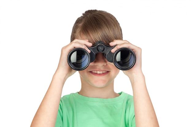 Muchacha que mira a través de los prismáticos aislados en el fondo blanco