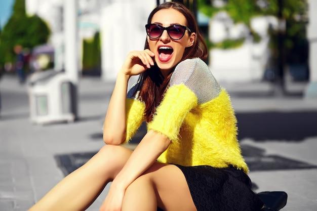 Muchacha que ríe con gafas de sol sentado en la calle