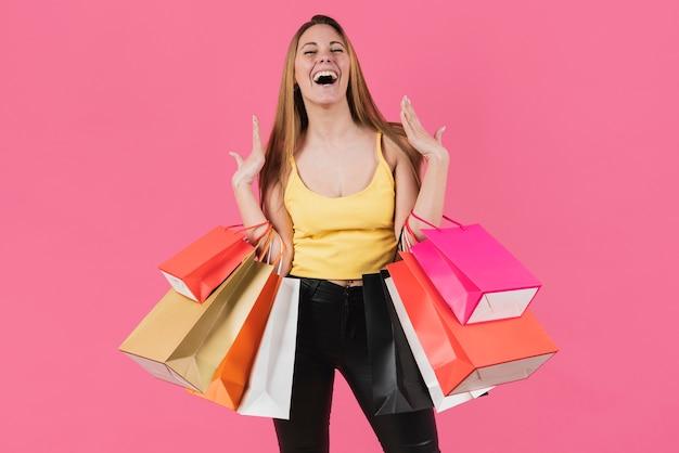 Muchacha que ríe que sostiene bolsos de compras en su brazo