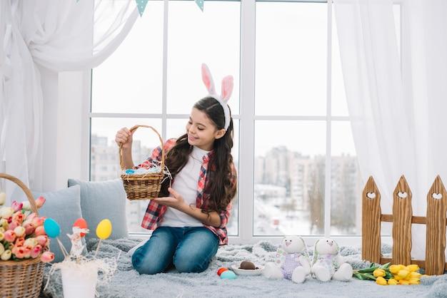 Muchacha que se sienta en la cama que mira la cesta de los huevos de pascua en casa