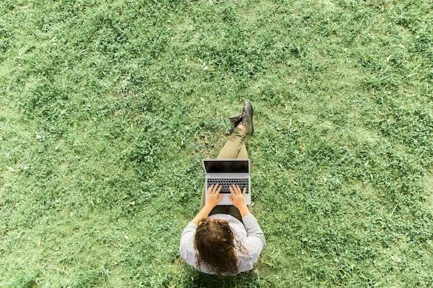 Muchacha que se sienta con el cuaderno en hierba en un parque