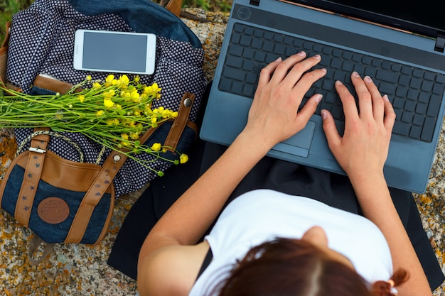 Muchacha que se sienta en hierba verde con las manos de la computadora portátil en el teclado.