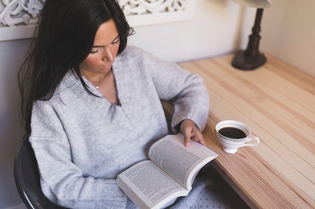 Una muchacha que se sienta en el libro de lectura de la silla con la taza de café en la tabla