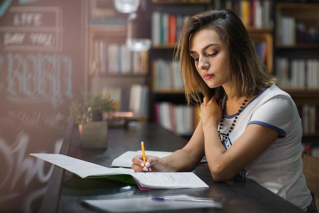 Muchacha que se sienta en la mesa con los cuadernos que escriben
