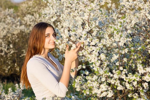 Muchacha que sonríe en el fondo de un árbol floreciente.