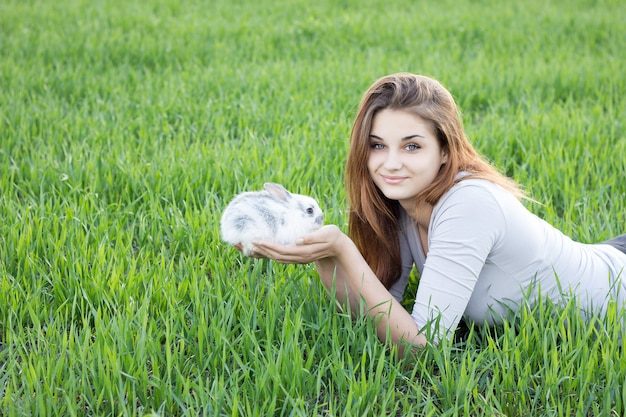 Muchacha que sostiene un conejo mientras que en un prado verde.