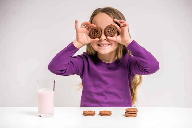 Muchacha que sostiene la galleta mientras que se sienta en la tabla.