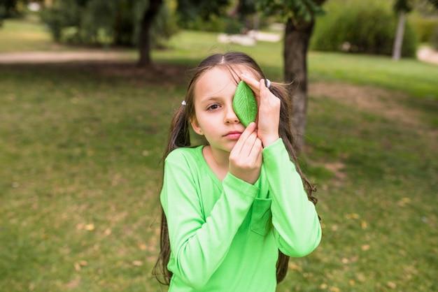Muchacha que sostiene la hoja verde artificial en su ojo izquierdo que se coloca en hierba