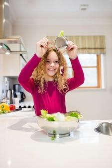 Muchacha que sostiene la lechuga en cuchara