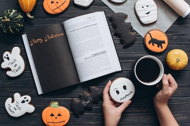 Muchacha que sostiene la taza de café, pan de jengibre para halloween y que lee el libro de terror en un fondo de madera negro.