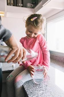 Muchacha que sostiene el vidrio mientras que su padre que vierte el agua en cocina