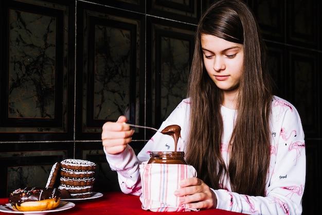 Muchacha que toma el chocolate derretido con la cuchara del tarro en la tabla