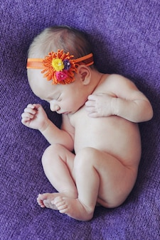 Muchacha recién nacida linda del primer que duerme en un fondo púrpura, colores brillantes del bebé el dormir