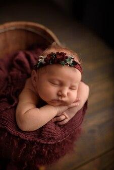 Muchacha recién nacida linda que duerme en una tina en un fondo de madera.