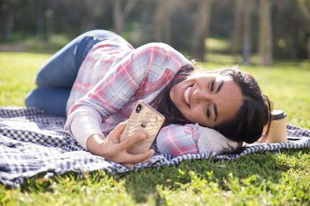Muchacha relajada alegre del estudiante que miente en la tela escocesa en parque