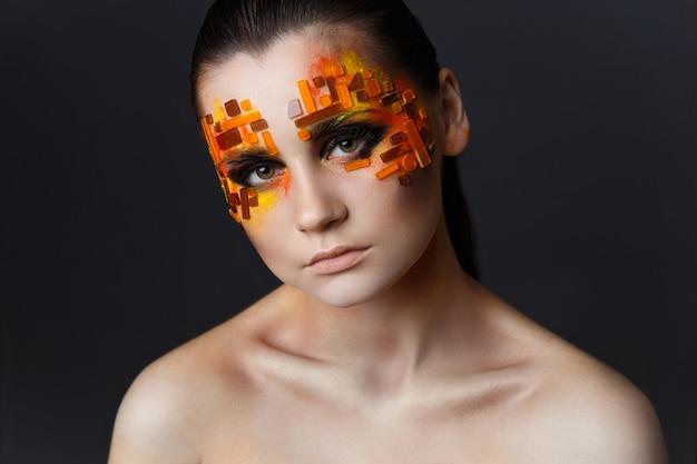 Muchacha con los rhinestones anaranjados y rojos en su cara.