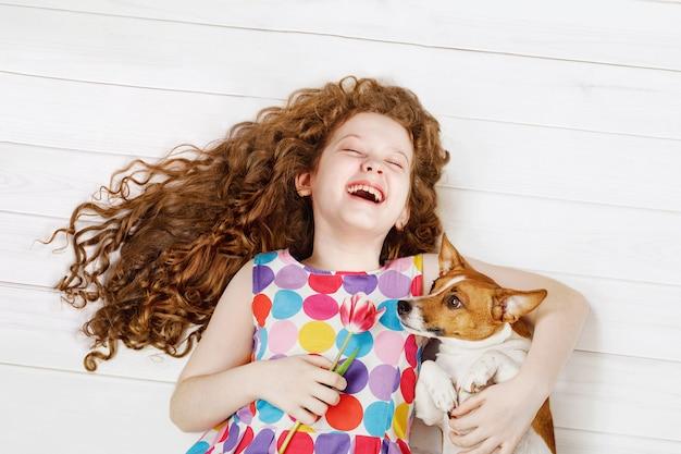 Muchacha de risa que abraza el perro que pone en un suelo de madera caliente.