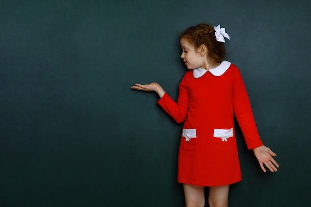 Muchacha rizada elegante cerca de la pizarra verde en sala de clase.