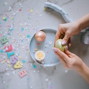 La muchacha rompe los huevos de pascua de oro en el fondo de mármol, confeti, chispas, cintas.