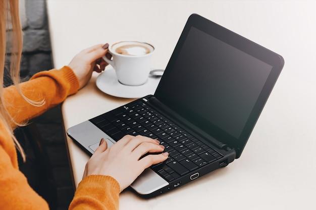 Muchacha rubia en un café con una computadora portátil y un café. freelancer de la chica joven que trabaja en una computadora portátil
