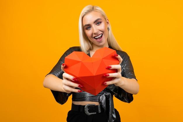 La muchacha rubia caucásica sostiene una figura del corazón 3d en una pared anaranjada
