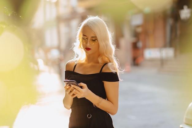 Muchacha rubia emocional en gafas de sol con el teléfono en sol del verano
