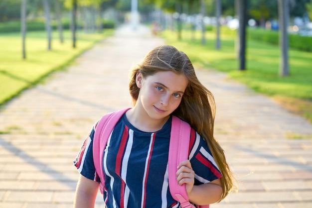 Muchacha rubia del estudiante del niño en el parque