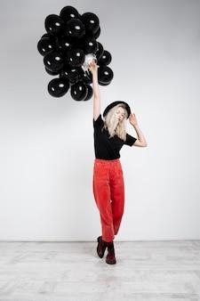Muchacha rubia hermosa joven que sostiene globos negros sobre la pared blanca.