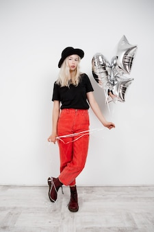 Muchacha rubia hermosa joven que sostiene los globos de plata sobre la pared blanca.